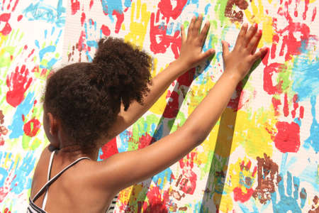 bilbo: Girl playing with paint. Handprints in different colors in a mural. Funny photo of a childrens activity, organized by the school. Casilda Iturrizar Park, Bilbao, Euskadi, Basque Country, Spain. Photo taken on: May 22nd, 2010.