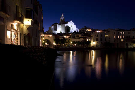 within: The church and a small beach in Cadaques at night. Cadaques, a small coastal town, is the small town of the Catalan painter Salvador Dali. The Church of Cadaques is a symbol in the village. The village is within a natural park. Girona, Costa Brava, Spain