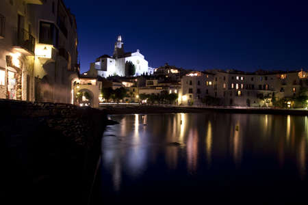 The church and a small beach in Cadaques at night. Cadaques, a small coastal town, is the small town of the Catalan painter Salvador Dali. The Church of Cadaques is a symbol in the village. The village is within a natural park. Girona, Costa Brava, Spain photo