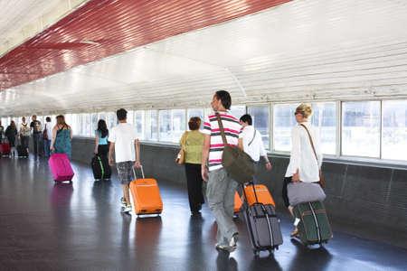 passenger vehicle: Pasajeros con equipaje apresurarse a conexi�n. El aeropuerto de Barcelona. Catalu�a, SpainBARCELONA, 6 de JUN: Pasajeros corriendo al respecto, en el aeropuerto de Barcelona, el 06 de junio de 2009. Pasajeros con equipaje caminando por un pasillo en el aeropuerto de Barcelona para la conexi�n