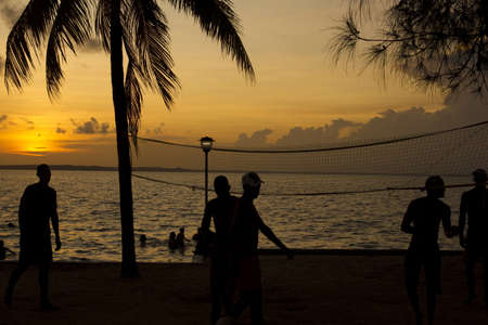 Silhouette of people playing beach volleyball at sunset photo