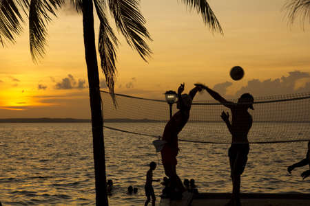 evening glow: Silhouette of people playing beach volleyball at sunset Stock Photo