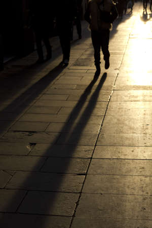 shadows of people walking down the street photo