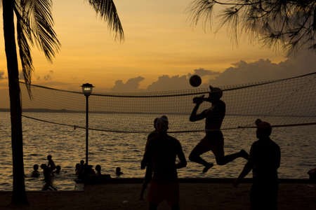 Silhouette of people playing beach volleyball at sunset Stock Photo