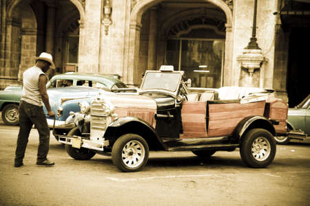 leverage: Havana, Cuba - September 9, 2011: A driver turns on an old car in the streets of Havana. Ancient light. Havana, Cuba. Cubans, unable to buy newer models, keep thousands of them running.Ford A, 1930 model.