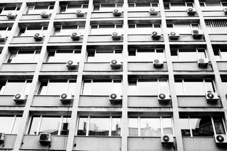 Exterior building with air conditioning in nearly every window  monochrome photo