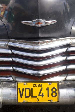 Close up, frontal view of a Classical American car with 'Cuba Havana' number plate.   CIENFUEGOS, CUBA-AUG 26: Classic Chevrolet on August 26, 2011 in Cienfuegos, Cuba. Cubans, unable to buy newer models, keep thousands of them running. The old cars have