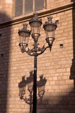 modernist: Modernist lamppost with his shadow in the Gothic Quarter of Barcelona, Spain