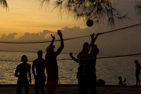 Silhouette of people playing beach volleyball at sunset