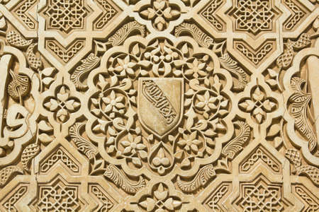 14th: Shield of the Nazari kingdom of Granada   Arabic stone engravings on the Alhambra palace wall in Granada, Spain Stock Photo