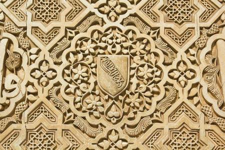 Shield of the Nazari kingdom of Granada   Arabic stone engravings on the Alhambra palace wall in Granada, Spain Stock Photo