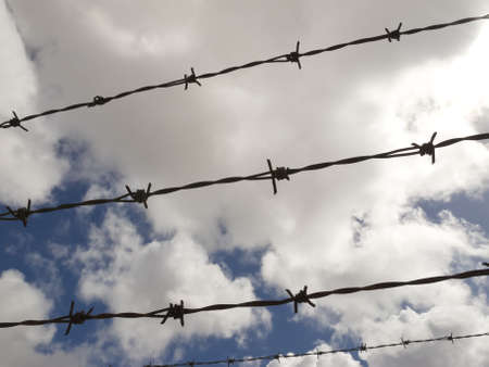 Barbed wire with a cloudy sky background photo