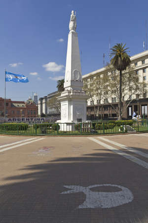evita: The Plaza de Mayo  English  May Square  is the main square in Buenos Aires, Argentina  In the background, the Casa Rosada  Pink House   The Piramide de Mayo in the middle  Painted on the floor, the symbol of the mothers and grandmothers of May