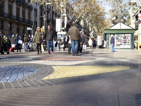 BARCELONA - DECEMBER 7: Tourists strolling famous Ramblas on December 7, 2012 in Barcelona. Rambla boulevard is one of the most recognized streets in the world.