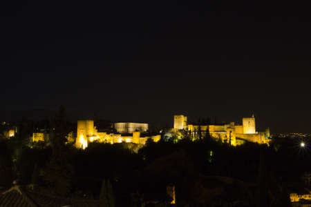 The complex of the Alhambra, the Nasrid palaces, the Palace of Charles V and the Torre de la Vela, at night. Granada, Spain