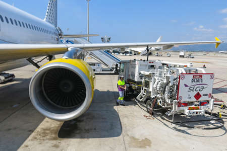 fuselage: BARCELONA- AUGUST 5: Airbus A320 of the Vueling Airlines receiving fuel from tanker truck at Barcelona International Airport on August 5, 2014 in Barcelona, Catalonia, Spain.