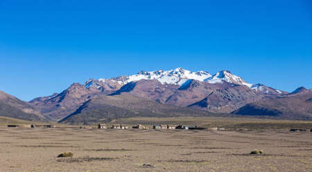 puna: Small village of shepherds of llamas in the Andean mountains. High Andean tundra landscape in the mountains of the Andes. The weather Andean Highlands Puna grassland ecoregion, of the montane grasslands and shrublands biome,