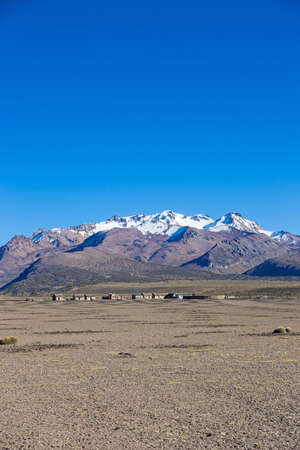 montane: Small village of shepherds of llamas in the Andean mountains. High Andean tundra landscape in the mountains of the Andes. The weather Andean Highlands Puna grassland ecoregion, of the montane grasslands and shrublands biome,
