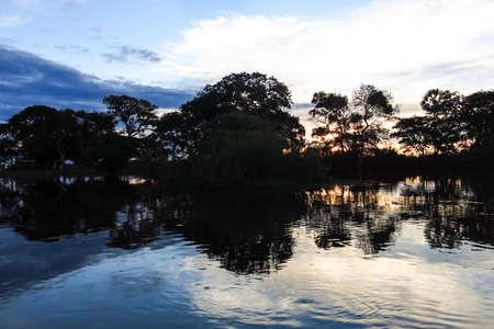 dawning: Sunset. Boat Crossing the Amazon.  Beni region, Pampas de Yacuma, Bolivia.