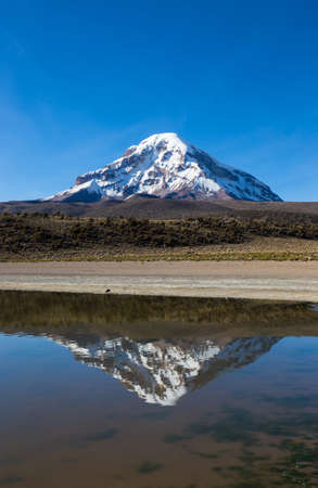 Sajama volcano and lake Huayñacota, in the Natural Park of Sajama. Bolivia Stock Photo