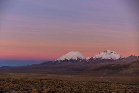 Sunset in Andes. Parinacota and Pomerade volcanos. High Andean landscape in the Andes. High Andean tundra landscape in the mountains of the Andes.