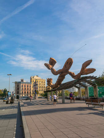 BARCELONA, SPAIN - OCT 5: people walking on a sunny morning on October 5, 2016, on the Walk 'Moll de la Fusta', on the coast of the city of Barcelona. In the background the estauas 'Gamba' and 'face Barcelona'
