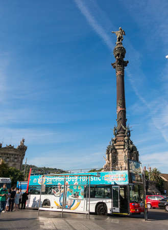 colonizer: BARCELONA, SPAIN - OCT 5: Tourists await the tourist bus, under the statue of Christopher Columbus on October 5, 2016 at the lower end of La Rambla.