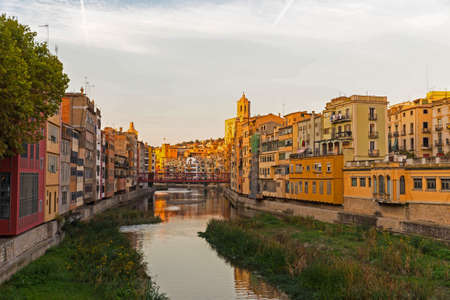 jewish houses: Onyar river crossing the downtown of Girona with bell tower of Basilica of Sant Feliu in background. Gerona, Costa Brava, Catalonia, Spain.