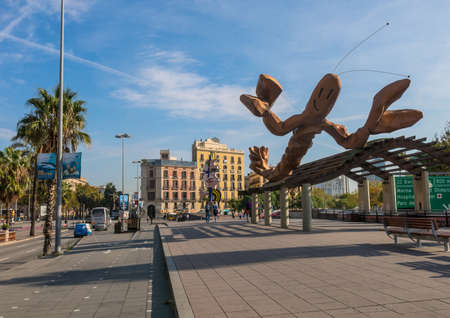 BARCELONA, Spanje - 5 oktober: voorbijgangers op een zonnige dag op 5 oktober 2016, op de Walk 'Moll de la Fusta', aan de kust van de stad Barcelona. Op de achtergrond de monumenten 'Gamba' & 'Barcelona Head' Redactioneel