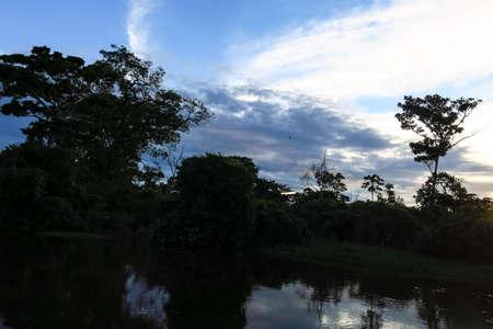 dawning: Yacuma river. Boat Crossing the Amazon.  Beni region, Pampas de Yacuma, Bolivia. The Yacuma River is a Bolivian Amazon River that flows through the department of Beni. Stock Photo