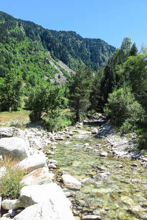 River of Aran valley in the Catalan Pyrenees, Spain. The main crest of Pyrenees forms a divide between France and Spain, with the microstate of Andorra sandwiched in between Stock Photo