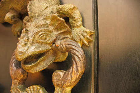 caller: Metal knocker shaped dragon. Spanish colonial style door. Cartagena de Indias, Colombia. Stock Photo