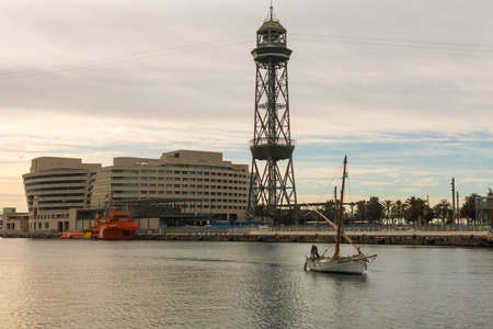 BARCELONA - MAR 1: Sunrise at the port of Barcelona, at the end of the Ramblas on March 1, 2017 in Catalonia, Spain. In the photo, a fishing boat, the World trade center building and the funicular tower