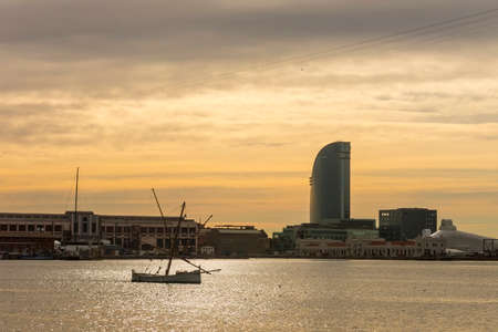 ramblas: Sunrise at the port of Barcelona, at the end of the Ramblas. In the photo, a fishing boat and sailing hotel. Barcelona, Spain Stock Photo