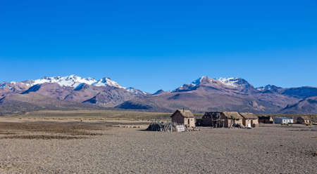 Small village of shepherds of llamas in the Andean mountains. High Andean tundra landscape in the mountains of the Andes. The weather Andean Highlands Puna grassland ecoregion, of the montane grasslands and shrublands biome,