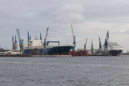famous industries: Hamburg, Germany - October 29, 2016. Transhipment cranes in Hamburg Sea Port. The Port of Hamburg is a sea port on the river Elbe in Hamburg, Germany. It is Germanys largest port and second largest in Europe Stock Photo