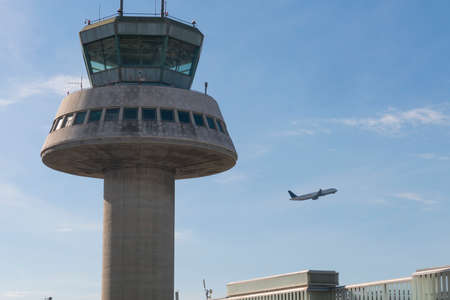 BARCELONA - OCT 16: Control tower on October 16, 2016 in Barcelona, Catalonia, Spain. The Prat-Barcelona International Airport is the busiest airport in SpainA plane flies next to the control tower at Barcelona Airport, Spain. The Prat-Barcelona Internati Editorial