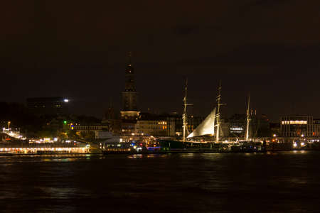 a nocturne: Hamburg, Germany - October 29, 2016. View of the St. Pauli Piers, one of Hamburgs major tourist attractions, with St Michaelis Church and The Gustav Adolf Church.