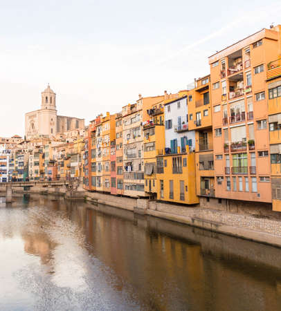 provinces: Onyar river crossing the downtown of Girona with bell tower of Basilica of Sant Feliu in background. Gerona, Costa Brava, Catalonia, Spain.
