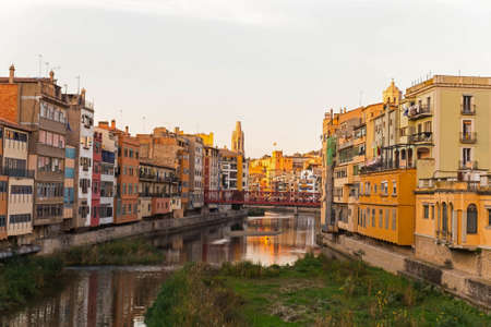 Onyar river crossing the downtown of Girona with bell tower of Basilica of Sant Feliu in background. Gerona, Costa Brava, Catalonia, Spain.
