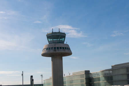 BARCELONA - OCT 16: A plane flies next to the control tower on October 16, 2016 in Barcelona, Catalonia, Spain. The Prat-Barcelona International Airport is the busiest airport in Spain  Control tower in Barcelona Airport, Catalonia, Spain.  The Prat-Barce Editorial