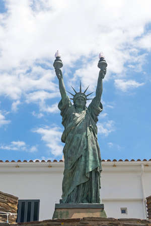 CADAQUES, SPAIN - JUNE 29, 2017: Statue of liberty, bronze. Sculpture inspired by Dalinian by the artist Bartholdi in 1994. Gift of Captain Moore to the municipality of Cadaqués, Spain.