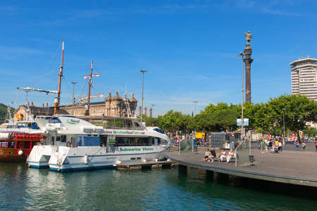 BARCELONA, SPAIN - MAY 16, 2017: Tourist boats moored near the Columbus statue, which run along the coast of Barcelona. End of the Ramblas. Barcelona, Spain