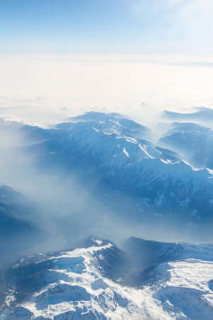Aerial view of the Swiss alps. Flying over Alps. Amazing view on mountain. Aerial view of misty mountains and clouds above the mountain peaks, blue tinted.
