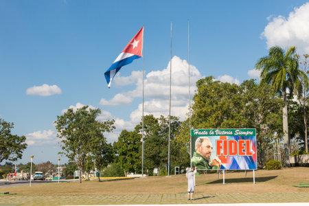 SANTA CLARA, CUBA-JANUARY 6, 2017: Poster with image of Fidel Castro and Cuban flag in the Plaza de la Revolución in the city of Santa Clara, Cuba. Next is the Mausoleum of homage to Ernesto Che Guevara. Editorial