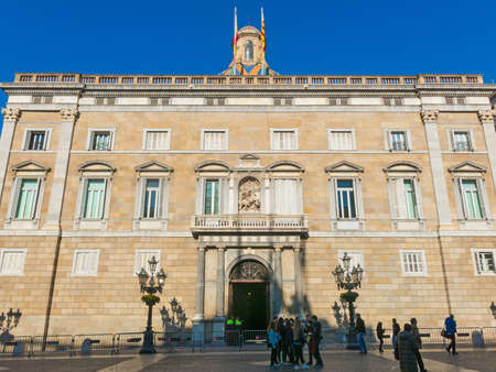 BARCELONA, SPAIN - FEBRUARY 15, 2018: People walk in front of the Generalitat Palace of Catalonia in Sant Jaume square. The palace houses the offices of the Presidency of the Generalitat of Catalonia. Barcelona, Spain.