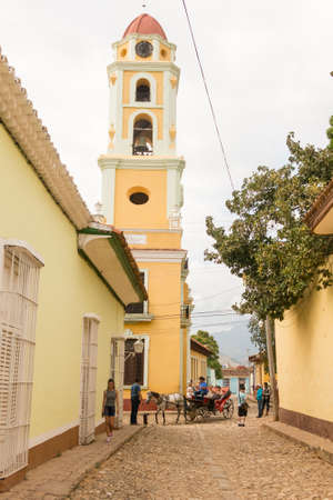 TRINIDAD, CUBA - JANUARY 4, 2017: A horse carriage walks through the historic center of Trinidad, in front of the Tower of National Museum Against Bandits. Urban scene in Trinidad, Cuba.