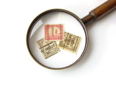 US postage stamps and magnifying glass on white background photo