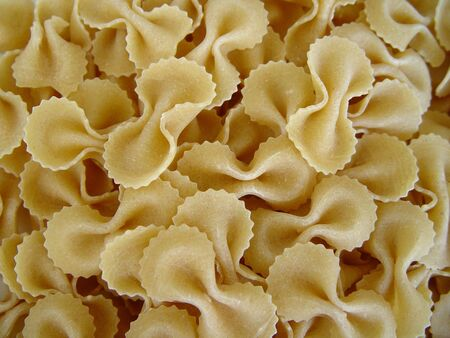 Raw pasta covering all the image background.          Stock Photo