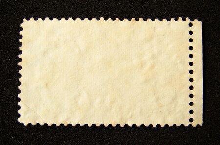 Blank postage stamp on black background. Stock Photo